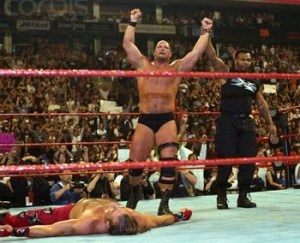 The torch is passed: Stone Cold has his hand raised in victory by Mike Tyson with Michaels down and out.